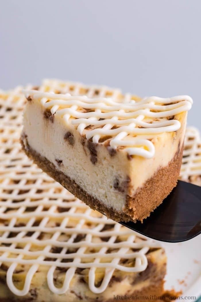 A spatula lifting up a piece of cheesecake.
