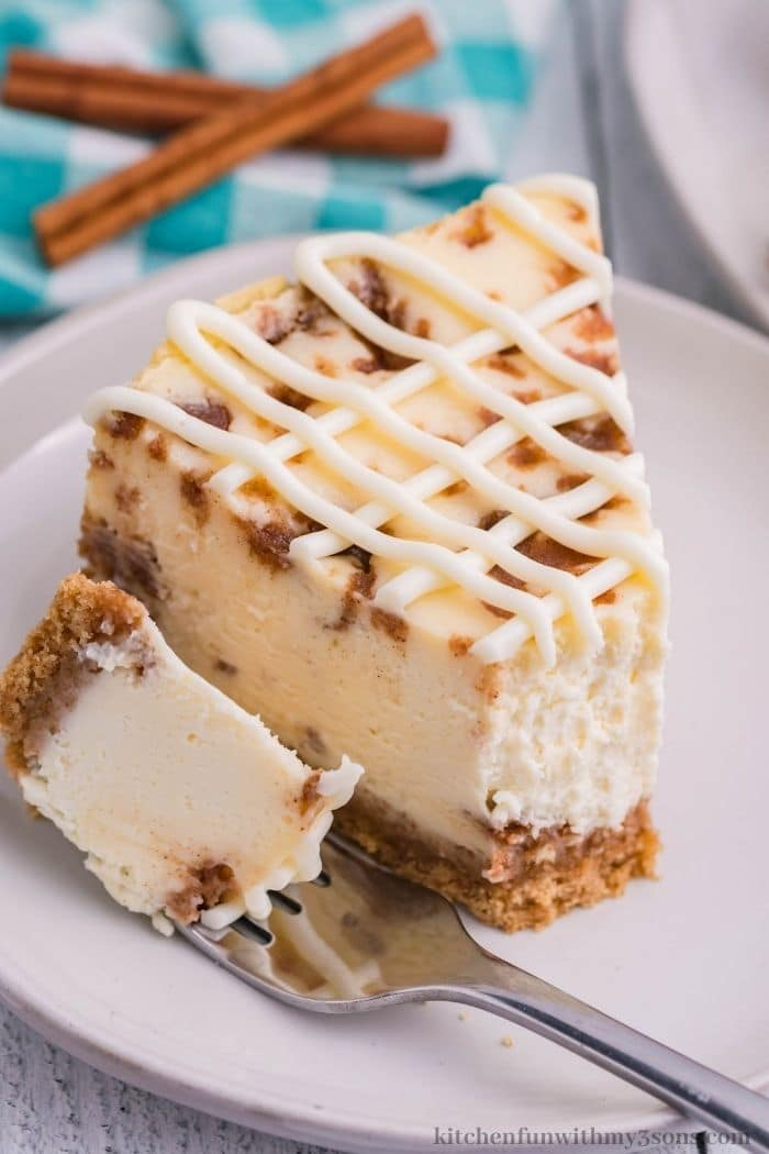 A piece of cinnamon roll cheesecake with a bite taken out.