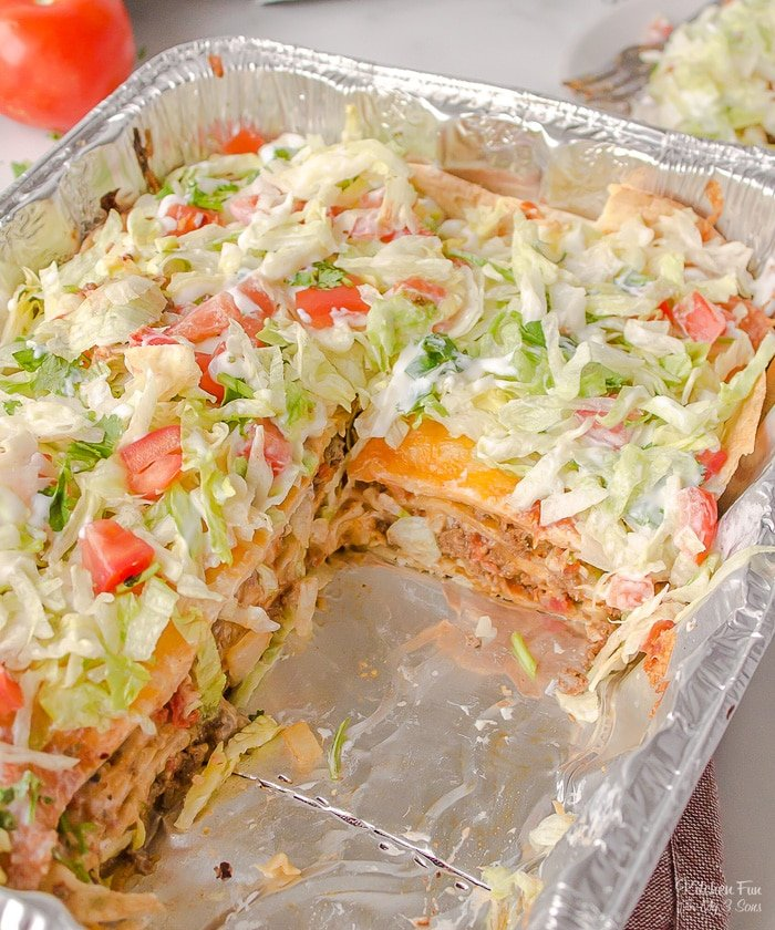 Taco Lasagna is a delicious, easy dinner with layers of beef, tortillas and seasoning, all topped with a homemade cheese sauce