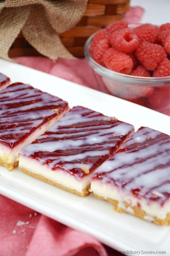 The raspberry bars on a rectangle platter.